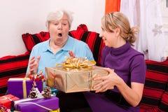 A mulher adulta começ um presente de um novo foto de stock