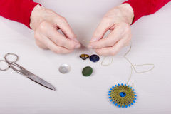 A mulher adulta costura em um botão Imagem de Stock Royalty Free