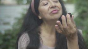Mulher adulta de encantamento que come bagas fora video estoque
