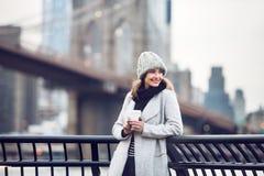 Mulher adulta de sorriso feliz do turista que guarda o copo de café de papel e que aprecia a opinião de New York City Imagem de Stock