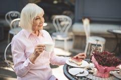 Mulher adulta deleitada que senta-se na tabela fora imagens de stock royalty free