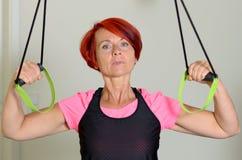 Mulher adulta desportiva que puxa abaixo de uma faixa da resistência imagens de stock