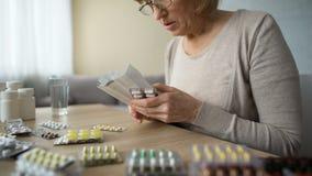 Mulher adulta doente que senta em casa a tabela e que lê a instrução dos comprimidos, medicina video estoque