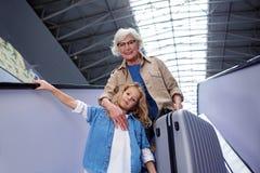 A mulher adulta e a menina otimistas estão movendo sobre a escadaria fotos de stock royalty free