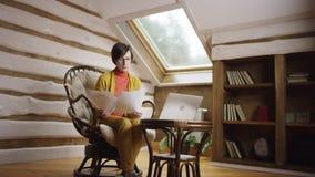 Mulher adulta em trabalhos dos vidros com documentos no portátil vídeos de arquivo
