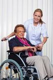 Mulher adulta em uma cadeira de rodas e em uma enfermeira Foto de Stock Royalty Free