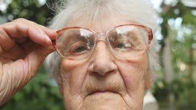 A mulher adulta endireita seus vidros e vista da câmera Retrato da avó exterior Feche acima do movimento lento filme