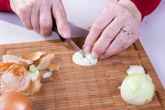 A mulher adulta está cortando cebolas Fotografia de Stock Royalty Free