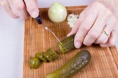 A mulher adulta está cortando o pepino Fotografia de Stock