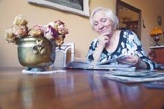 A mulher adulta está olhando um álbum com fotos velhas fotografia de stock