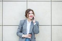 A mulher adulta está perto da parede com café Comunique-se pelo telefone Copie o espa?o Conceito do estilo de vida, urbano, negóc imagem de stock royalty free