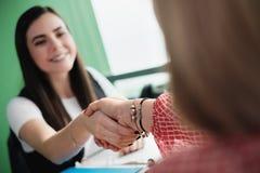 Mulher adulta feliz que agita as mãos com o corretor amigável do seguro de saúde foto de stock royalty free