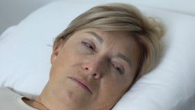 Mulher adulta fraca que encontra-se na cama, olhos de abertura após o sono, centro de reabilitação video estoque