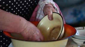 A mulher adulta lava pratos vídeos de arquivo