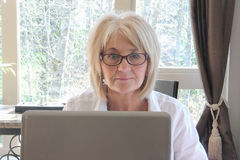 Mulher adulta madura que trabalha no computador. Foto de Stock