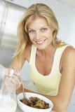 Mulher adulta meados de que come o cereal com fruta imagens de stock