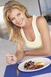 Mulher adulta meados de que come o pequeno almoço insalubre imagens de stock royalty free