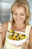 Mulher adulta meados de que come uma bacia de fruta fresca fotografia de stock royalty free