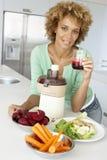 Mulher adulta meados de que faz o suco do legume fresco imagens de stock royalty free