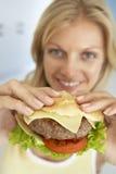 Mulher adulta meados de que prende um Hamburger imagens de stock royalty free