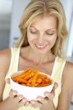 Mulher adulta meados de que prende uma bacia de cenouras imagem de stock