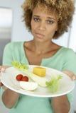 Mulher adulta meados de que prende uma placa do alimento saudável Fotografia de Stock Royalty Free