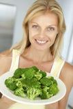 Mulher adulta meados de que prende uma placa dos bróculos imagens de stock