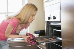 Mulher adulta meados de que remove a bandeja do cozimento do forno na cozinha Imagem de Stock