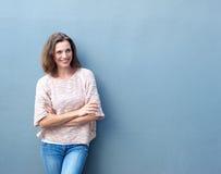 Mulher adulta meados de sorriso que está com os braços cruzados foto de stock