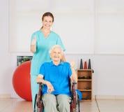 Mulher adulta na cadeira de rodas que mantém os polegares Fotos de Stock Royalty Free
