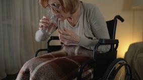 Mulher adulta na cadeira de rodas que toma o comprimido com agitação das mãos, vida triste no lar de idosos video estoque