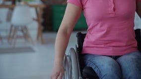 Mulher adulta na cadeira de rodas que vai para a frente em casa video estoque