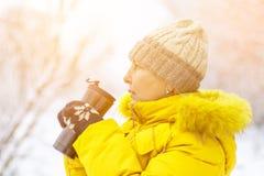Mulher adulta no revestimento amarelo do inverno que aprecia o café em um dia de inverno fotos de stock royalty free