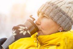 Mulher adulta no revestimento amarelo do inverno que aprecia o café em um dia de inverno imagem de stock royalty free