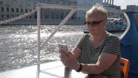 Mulher adulta no smartphone da terra arrendada do navio do turista vídeos de arquivo