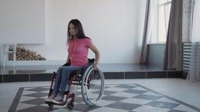 Mulher adulta no tempo da despesa da cadeira de rodas em casa filme