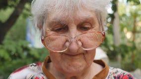 Mulher adulta nos monóculos que lê algo e o sorriso exteriores Retrato da avó feliz nos vidros que passa o tempo fora filme