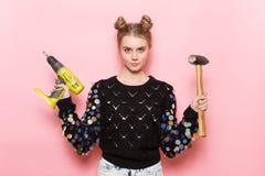 Mulher adulta nova bonito que guarda ferramentas de funcionamento nas mãos Imagem de Stock