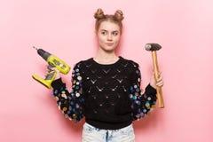 Mulher adulta nova bonito que guarda ferramentas de funcionamento nas mãos Imagem de Stock Royalty Free