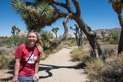 A mulher adulta nova começa uma caminhada nas grandes árvores de Joshua Tree National Park imagens de stock royalty free