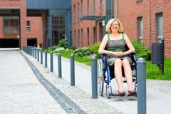 Mulher adulta nova na cadeira de rodas na rua Fotografia de Stock