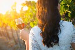 Mulher adulta nova que aprecia o vidro da degustação de vinhos que anda no vinhedo imagens de stock