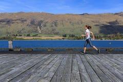 Mulher adulta nova que corre no cais Foto de Stock