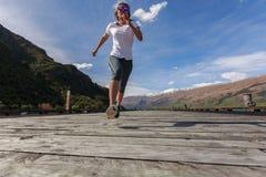 Mulher adulta nova que corre no cais Fotografia de Stock Royalty Free