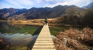 Mulher adulta nova que está apenas na ponte no lago Moke, Que Foto de Stock Royalty Free