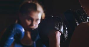 Mulher adulta nova que faz o treinamento kickboxing com seu treinador video estoque