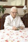A mulher adulta que conta o dinheiro ao sentar-se na tabela Imagens de Stock