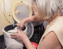 Mulher adulta que cozinha o arroz japonês branco em uma bandeja elétrica fotos de stock