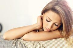 Mulher adulta que descansa no sofá Fotografia de Stock Royalty Free
