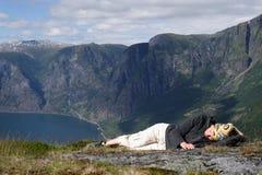 Mulher adulta que dorme nas montanhas imagem de stock